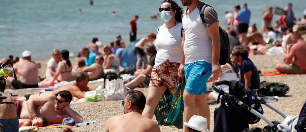 Una mujer con una máscara es vista en la playa de Southend tras el brote de la enfermedad coronavirus (COVID-19), Southend, Gran Bretaña, 25 de mayo de 2020.