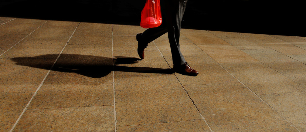 A pedestrian carries a plastic bag while walking down the street in New York, U.S., April 2, 2019.  REUTERS/Lucas Jackson
