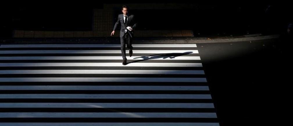 A businessman crosses a road at Tokyo's business district, Japan January 20, 2016.  REUTERS/Toru Hanai/File Photo - S1AETLCQKAAA