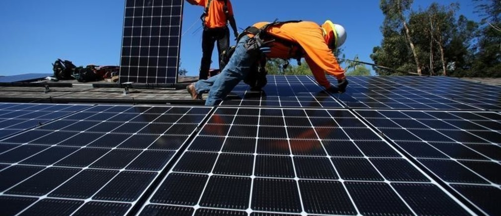 Solar installers from Baker Electric place solar panels on the roof of a residential home in Scripps Ranch, San Diego, California, U.S. October 14, 2016.