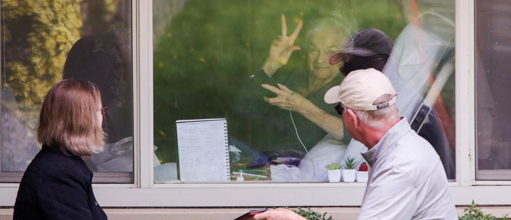 Judie Shape, de 81 años, que dio positivo en el test de coronavirus, recibe la visita de su hija Lori Spencer y su marido Michael Spencer en Kirkland, Washington.