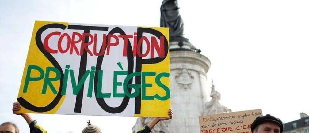 """A man holds a banner as he attends a demonstration against the corruption of elected representatives at Place de la Republique in Paris, France February 25, 2017. The banner reads """"Stop corruption and privileges"""". REUTERS/Gonzalo Fuentes - RC1C4F109D10"""
