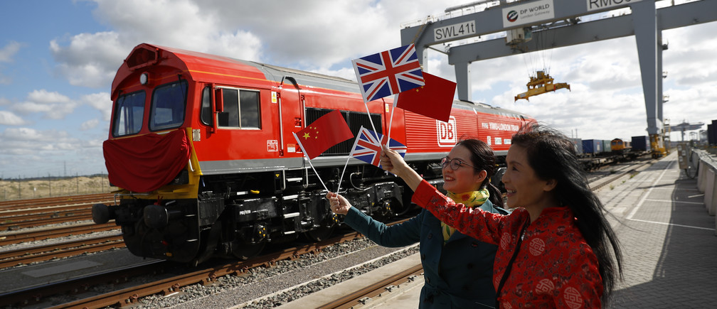 Chinese women wave flags at the official ceremony to mark the departure of the first UK to China export train, laden with containers of British goods, from the DP World London Gateway, Stanford-le-Hope, Britain April 10, 2017. REUTERS/Peter Nicholls - LR1ED4A0PDTXT