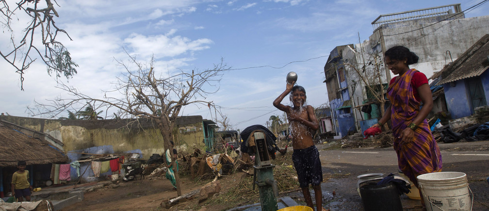 A boy bathes at a public hand pump after Cyclone Phailin hit Gopalpur in Ganjam district in the eastern Indian state of Odisha October 13, 2013. India's strongest storm in 14 years left a trail of destruction along the country's east coast on Sunday, but little loss of life was reported after close to a million people took refuge in shelters. Cyclone Phailin was expected to dissipate within 36 hours, losing momentum as it headed inland after making landfall on Saturday from the Bay of Bengal, bringing winds of more than 200 kph (125 mph) to rip up homes and tear down trees. REUTERS/Ahmad Masood (INDIA - Tags: ENVIRONMENT DISASTER) - GM1E9AE005Z01