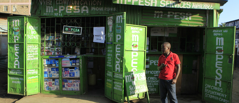 A man waits for M-Pesa customers at his shop in Kibera in Kenya's capital Nairobi December 31, 2014