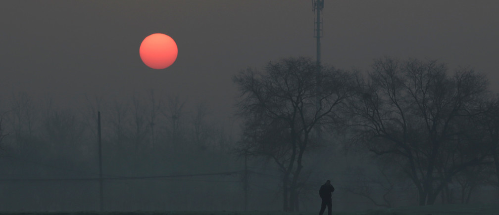 A man walks during sunrise in smog on a polluted day as a red alert issued for air pollution in Beijing, China, December 19, 2016. REUTERS/Jason Le