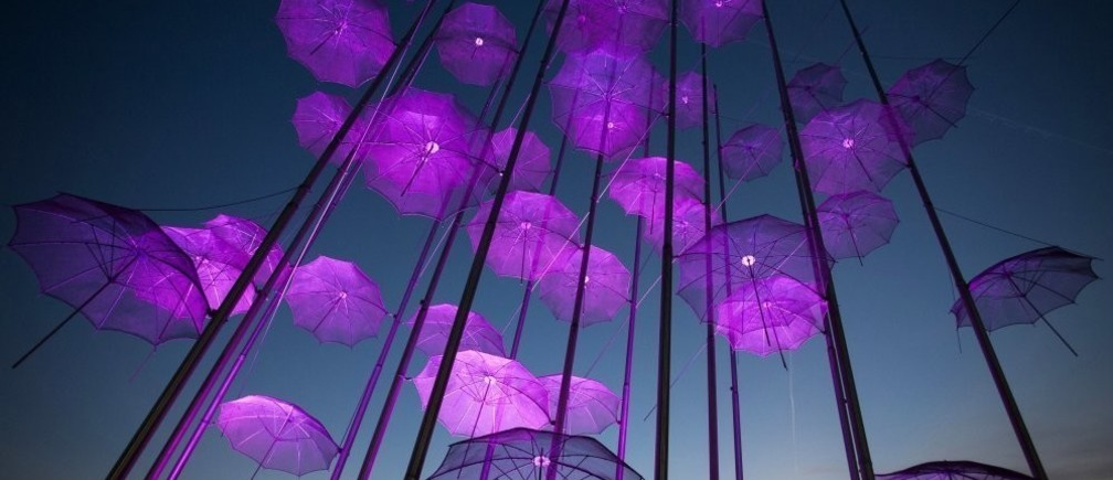 """""""Umbrellas"""", the sculpture by Giorgos Zogolopoulos is illuminated in pink light to mark Breast Cancer Awareness Month in Thessaloniki in northern Greece October 21, 2014. REUTERS/Alexandros Avramidis (GREECE - Tags: HEALTH SOCIETY TPX IMAGES OF THE DAY)"""
