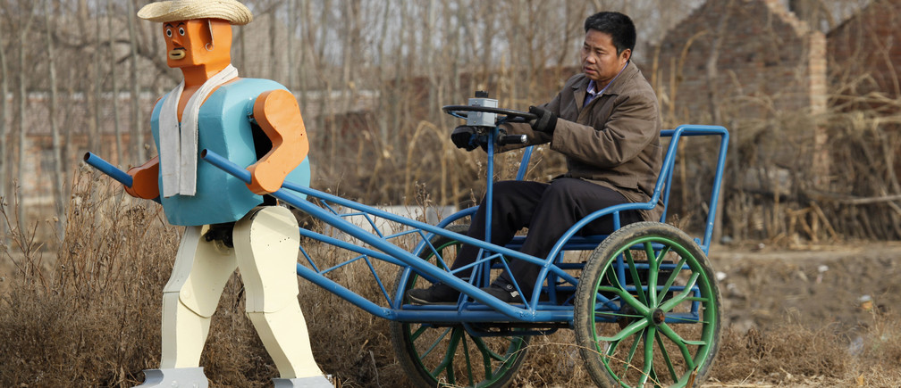 Farmer Wu Yulu drives his rickshaw pulled by a his home-made walking robot near his home in a village at the outskirts of Beijing January 8, 2009. This robot is the latest and largest development of hobby inventor Wu, who started to build robots in 1986, made of wire, metal, screws and nails found in rubbish sites.