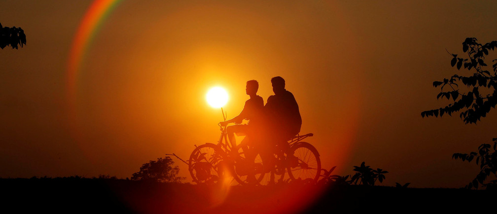 Boys are silhouetted against the setting sun as they ride bicycles on the outskirts of Agartala, India, November 21, 2016