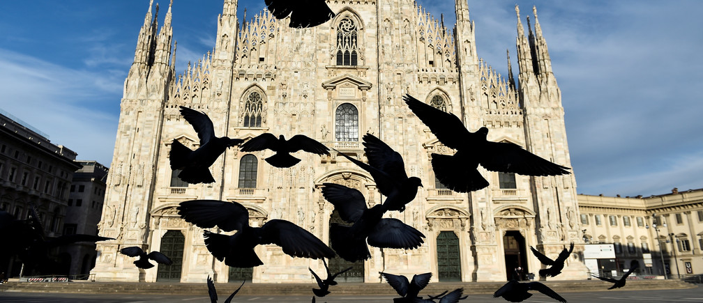 A pigeons fly in front of the Duomo Cathedral, amidst the coronavirus disease (COVID-19) spread, on Easter Sunday, in Milan, Italy, April 12, 2020. REUTERS/Flavio Lo Scalzo - RC243G9SREUW