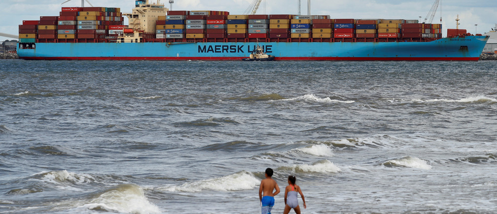 Children play in the sea at New Brighton as the Maersk Line container ship Maersk Sentosa is helped by tugs as it navigates the River Mersey in Liverpool, Britain, July 31, 2018. REUTERS/Phil Noble