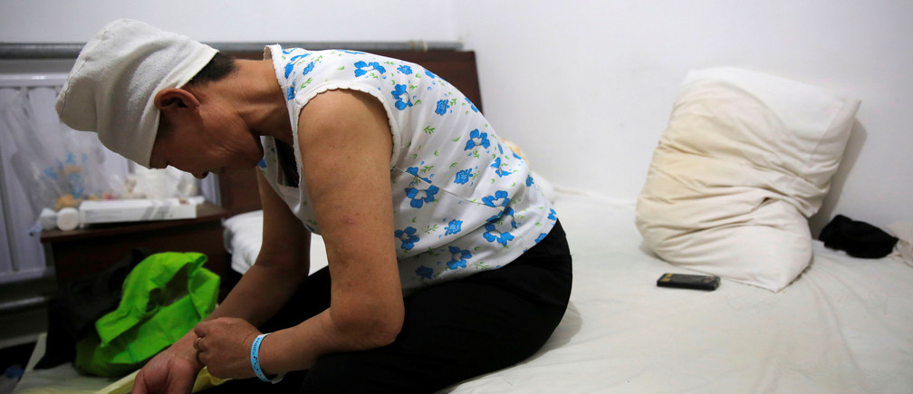 """Huang sits on a bed in her room at the accommodation where patients and their family members stay while seeking medical treatment in Beijing, China, June 22, 2016. Huang, who suffers from rectal cancer, came from Inner Mongolia to seek treatment at a specialist hospital in Beijing. REUTERS/Kim Kyung-Hoon   SEARCH """"HOSPITAL ACCOMMODATION"""" FOR THIS STORY. SEARCH """"WIDER IMAGE"""" FOR ALL STORIES. - D1BEUEBQCLAA"""