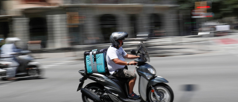 A scooter rider wearing a Deliveroo backpack drives in the central Barcelona, Spain, July 23, 2019.