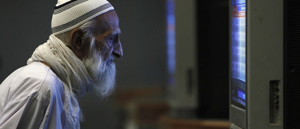 An elderly man monitors share prices on a television screen during a trading session inside the Karachi Stock Exchange December 20, 2010. REUTERS/Akhtar Soomro (PAKISTAN - Tags: BUSINESS IMAGES OF THE DAY) - RTXVWDZ