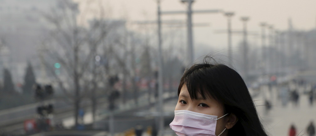 A school girl wearing a protective mask makes her way in a shopping district as China's capital Beijing braces for four days of choking smog starting Saturday, in Beijing, China, December 19, 2015. REUTERS/Kim Kyung-Hoon - GF10000271179