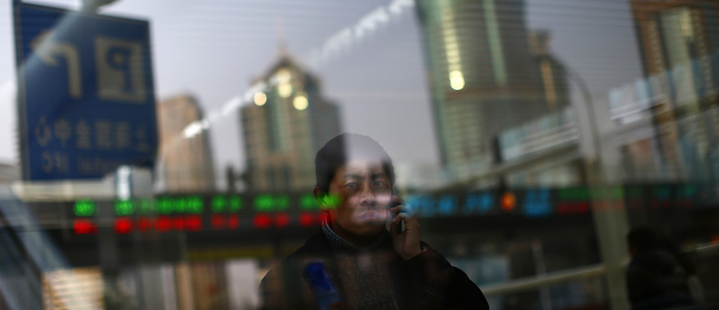 A man walks out of a subway station as he talk on the phone at the financial district of Pudong in Shanghai March 11, 2014.