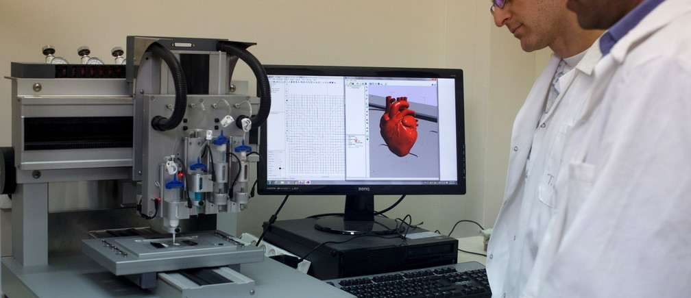 Professor Tal Dvir (R) and a researcher stand next to a 3-D printer during their interview with Reuters about their development of a 3D printed patch comprised of lab-grown heart tissue and nano-electronics that could potentially revolutionize the treatment of heart disease, at a laboratory in Tel Aviv University March 16, 2016. Picture taken March 16, 2016. REUTERS/ Nir Elias - RTSCT4Y