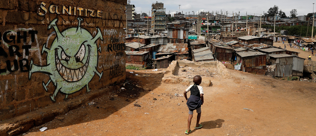 A boy walks in front of a graffiti promoting the fight against the coronavirus disease (COVID-19) in the Mathare slums of Nairobi, Kenya, May 22, 2020. REUTERS/Baz Ratner     TPX IMAGES OF THE DAY - RC2QTG9RR87Z