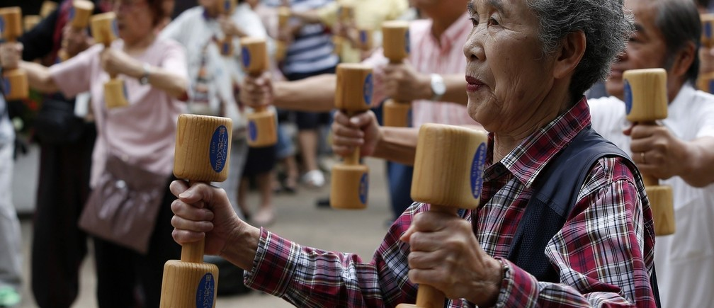 """People use wooden dumbbells during a health promotion event to mark Japan's """"Respect for the Aged Day"""" at a temple in Tokyo's Sugamo district, an area popular among the Japanese elderly, September 15, 2014. The population aged over 65 in Japan reaches about 33 million, which is the highest number in the history meaning one out of every four people is 65 or older, according to the government survey."""