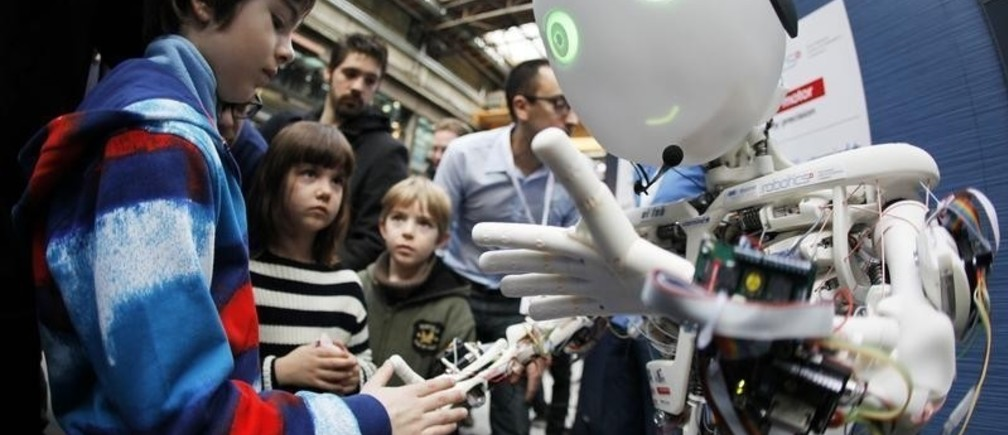 Children interact with the humanoid robot Roboy at the exhibition Robots on Tour in Zurich, March 9, 2013. A project team composed of scholars and industry representatives developed the prototype of the tendon driven humanoid robot Roboy within nine months. Roboy was unveiled to the public today during the exhibition that is marking the 25th anniversary of the Artificial Intelligence Laboratory of the University of Zurich (AI Lab). Picture taken with fish-eye lens