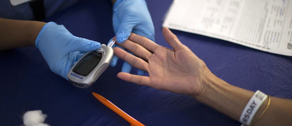 A person receives a test for diabetes during Care Harbor LA free medical clinic in Los Angeles, California September 11, 2014.