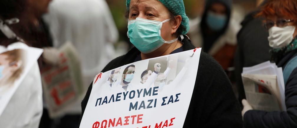 Un trabajador médico sostiene un letrero, con una máscara protectora, durante una protesta fuera de un hospital, mientras el brote de la enfermedad coronavirus (COVID-19) continúa en Atenas, Grecia, el 7 de abril de 2020.