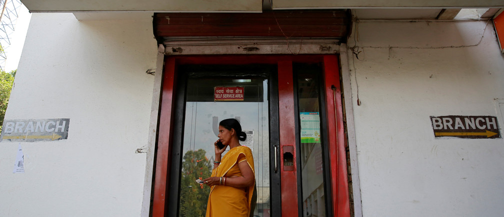 A woman speaks on her mobile phone outside a Punjab National Bank (PNB) branch in New Delhi, India, February 27, 2018. REUTERS/Saumya Khandelwal - RC12B3678870
