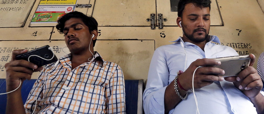 Commuters watch videos on their mobile phones as they travel in a suburban train in Mumbai, India, April 2, 2016. With smartphone sales booming and India preparing for nationwide 4G Internet access, India's film and TV industry hopes the ease of tapping your phone for the latest release will generate profits at last, overcoming the problems of woefully few cinemas and rampant piracy. Picture taken April 2, 2016. REUTERS/Shailesh Andrade - GF10000368981