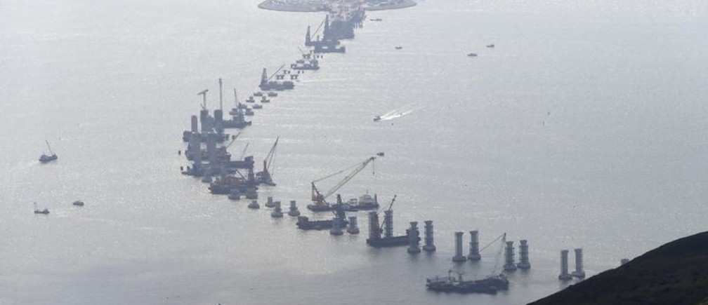 The Hong Kong-Zhuhai-Macao Bridge (HZMB), which will link the three cities in the Pearl River Delta, is seen under construction off Hong Kong's Lantau Island, China, June 12, 2015. HSBC is betting infrastructure construction in China's Pearl River Delta will turn the prosperous region of 40,000 square kilometres into a seamless metropolis that can fuel the bank's growth in the next decade. However, fundamental pieces of construction for the region are behind schedule. Hong Kong's transport minister said in January that a network of bridges and tunnels to link Hong Kong, Macau and the city of Zhuhai across the Pearl River Delta will not be finished by its 2016 target date amid rising costs. Picture taken June 12, 2015.