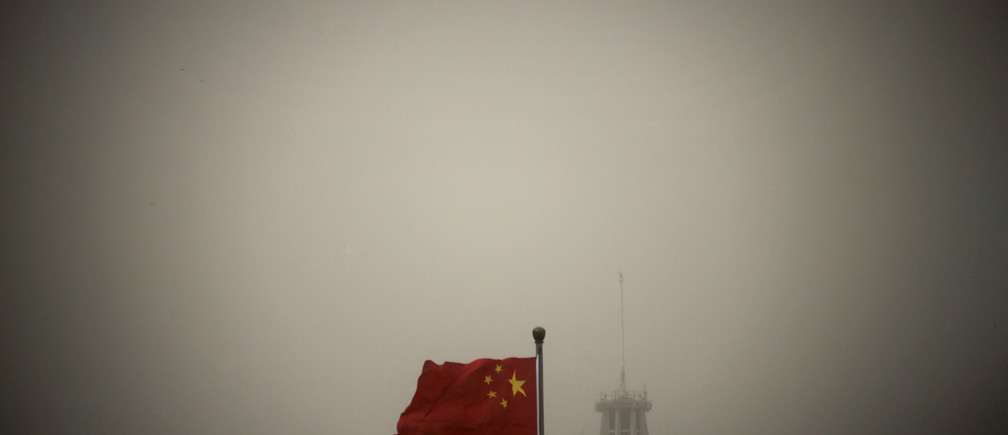 A Chinese national flag flies in front of Beijing Telegraph Building on a hazy morning in central Beijing, February 28, 2013. Beijing's environmental authorities said on Thursday air quality in Beijing and nearby regions hit dangerous levels, Xinhua News Agency reported. REUTERS/Petar Kujundzic (CHINA - Tags: ENVIRONMENT TPX IMAGES OF THE DAY) - GM1E92S186Z01