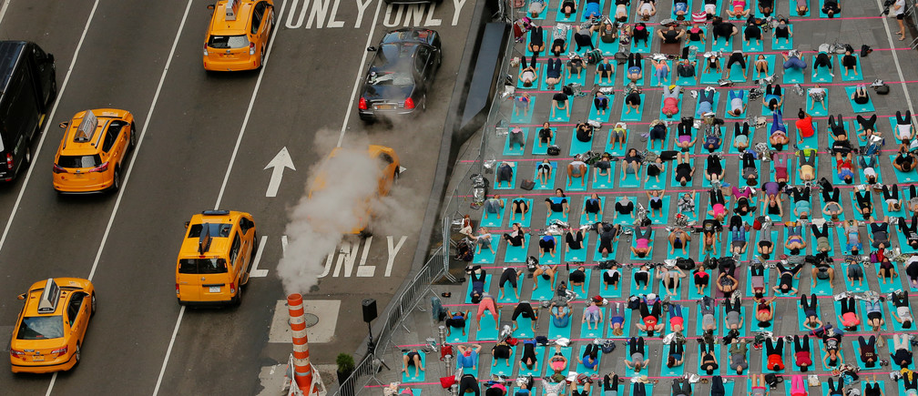 People participate in a yoga class during an annual Solstice event in the Times Square district of New York, U.S., June 21, 2017. REUTERS/Lucas Jackson      TPX IMAGES OF THE DAY - RTS1816B