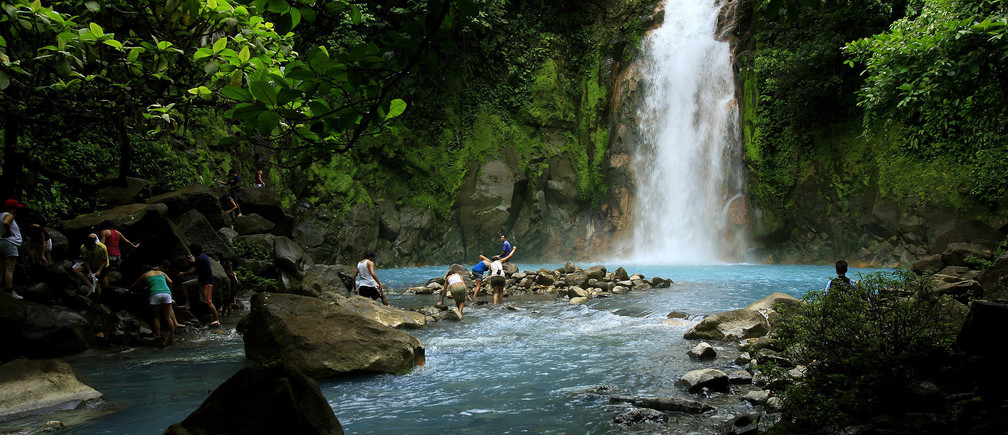 People swim in the Celeste river waterfall at Tenorio Volcano National Park in Upala March 18, 2008. The blue color of the lagoon, formed from chemical reactions of calcium carbonate and sulfur, is surrounded by amazing rainforest of 12,819 hectares of this park. The Celeste river carries its color for a distance of 36 km (22 miles). REUTERS/Juan Carlos Ulate (COSTA RICA) - GM1E43J0V1A01