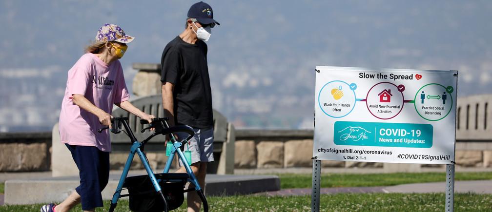 Una pareja de ancianos usan máscaras cuando hacen ejercicio en un parque.