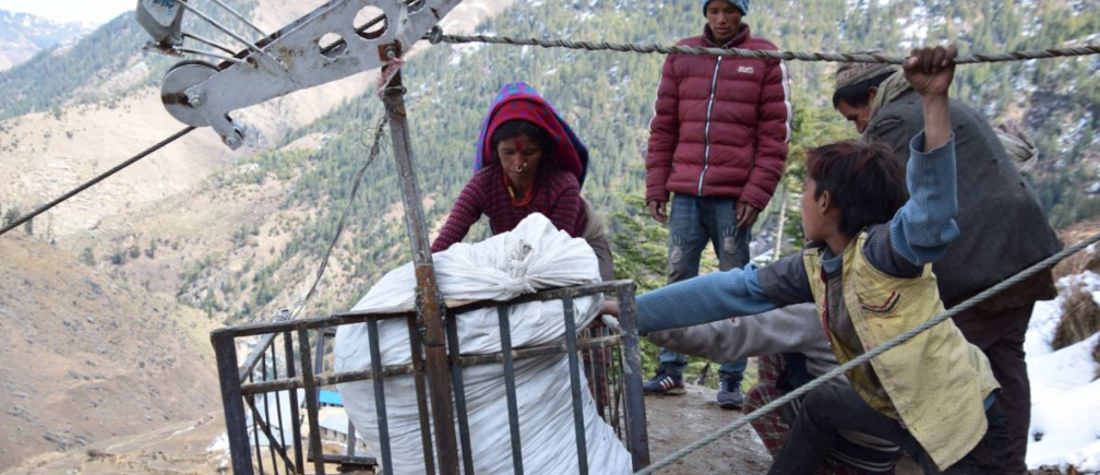 Belkosha Bohora loads produce into a gravity-assisted rope-and-cable system that lets women transport heavy loads to market without carrying them on their backs, in Ratada, Nepal, February 5, 2019. Credit: Archana Gurung, Practical Action