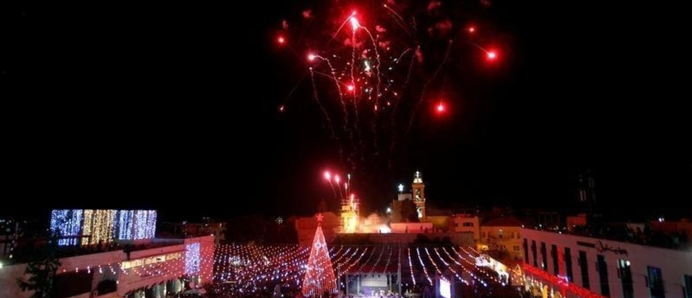 Fireworks explode during a Christmas tree lighting ceremony outside the Church of the Nativity in the West Bank town of Bethlehem, December 2, 2017. REUTERS/Mussa Qawasma - RC1C486E8A20