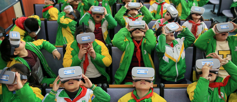 Primary school students wear virtual reality (VR) headsets inside a classroom in Xiangxi Tujia and Miao Autonomous Prefecture, Hunan province, China March 14, 2018. Picture taken March 14, 2018. REUTERS/Stringer