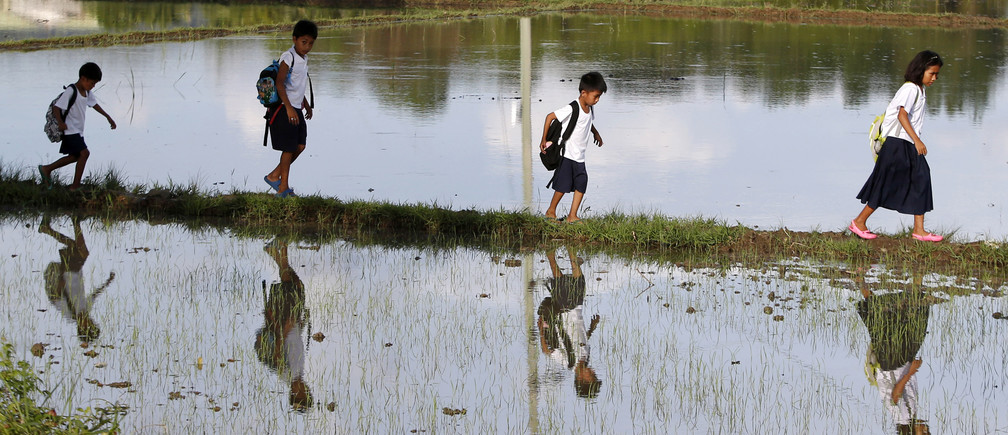 Grade school pupils are reflected in the water as they walk between rice paddy fields, on their way home after attending classes in Mogpog, Marinduque, August 19, 2014. The students said they walk for more than two kilometres, including walking between rice paddy fields, from Monday to Friday to go to school and back home. REUTERS/Erik De Castro (PHILIPPINES - Tags: SOCIETY EDUCATION) - GM1EA8J1G3001
