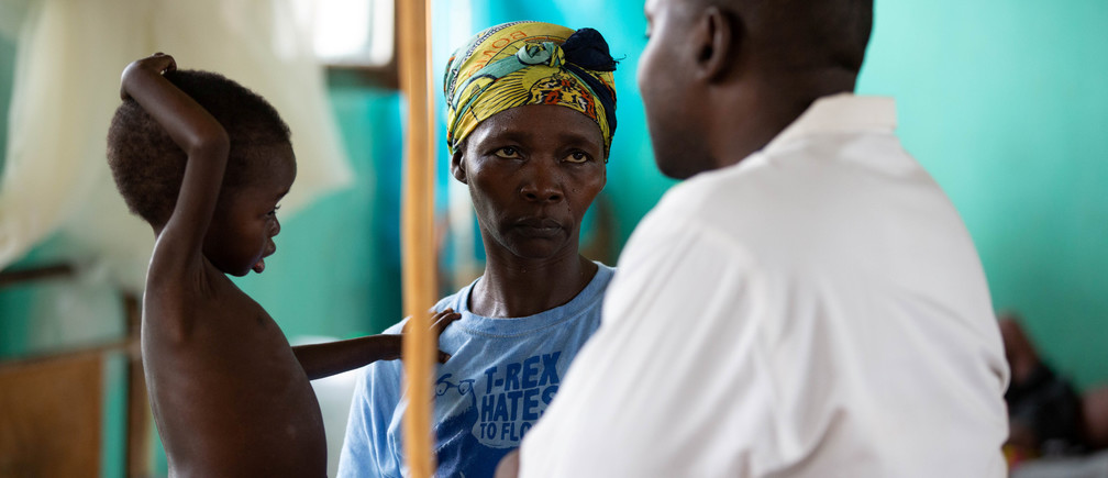 Three-year-old Eme Mbisa, who has become malnourished as a result of a measles infection, rests her hand on the shoulder of her mother, Marianne Mbisa, as she talks to a doctor in the measles isolation ward in Boso-Manzi hospital in Mongala province in northern Democratic Republic of Congo February 29 , 2020. Picture taken February 29 , 2020. REUTERS/Hereward Holland - RC2LPF92U3B4