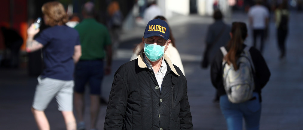A man, wearing a protective mask, walks through an empty street due to the coronavirus outbreak in central Madrid, Spain, March 14, 2020.