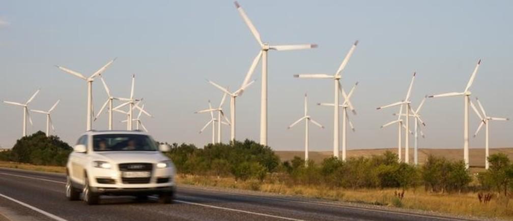 A car drives pastpower-generating windmill turbines in Zhambyl region, southern Kazakhstan September 3, 2017.  REUTERS/Shamil Zhumatov