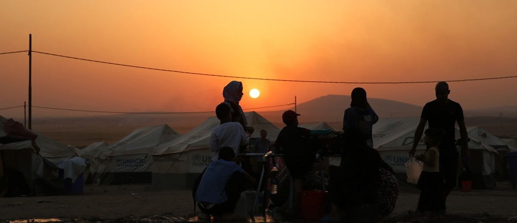 raqi refugees, who fled from the violence in Mosul, use containers to collect water during sunset inside the Khazer refugee camp on the outskirts of Arbil, in Iraq's Kurdistan region, June 27, 2014.
