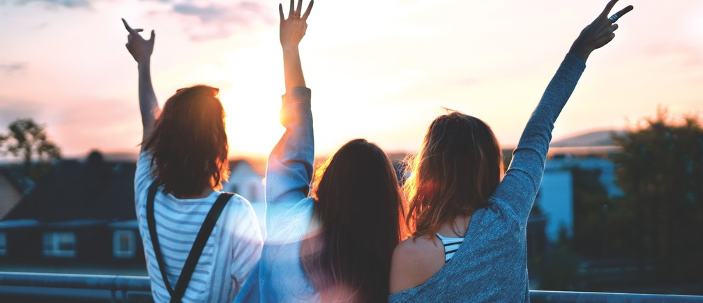 Three young women enjoying a sunset.