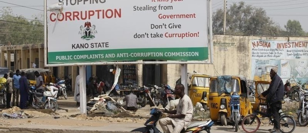 A man on a motorcycle sits near a signboard campaigning against corruption along a road in Dangi district in Nigeria's northern city of Kano, January 19, 2016. True to his election promises, Nigerian President Muhammadu Buhari has gone all out on corruption, alleging mind-boggling sums plundered from state coffers and giving investigators licence to pull in big hitters once thought untouchable. Now comes the hard part: making the charges stick. The first test comes on Wednesday with the opening of the trial of former National Security Advisor Sambo Dasuki, accused of fraud over $68 million of defence spending, part of a wider $2.1 billion in arms deals under scrutiny