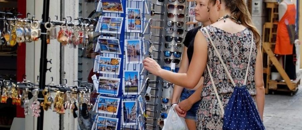 Tourists look at postcards at a souvenir shop in the Old Town of Valencia, Spain August 17, 2017. REUTERS/Heino Kalis