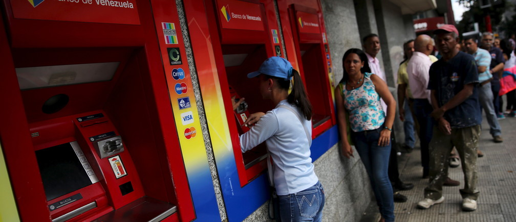 Venezuelans line up to withdraw cash from an automated teller machine (ATM) outside a Venezuela branch in Caracas December 4, 2015. Polarized Venezuela heads to the polls this weekend with a punishing recession forecast to rock the ruling Socialists and propel an optimistic opposition to its first legislative majority in 16 years. REUTERS/Nacho Doce - GF10000254959