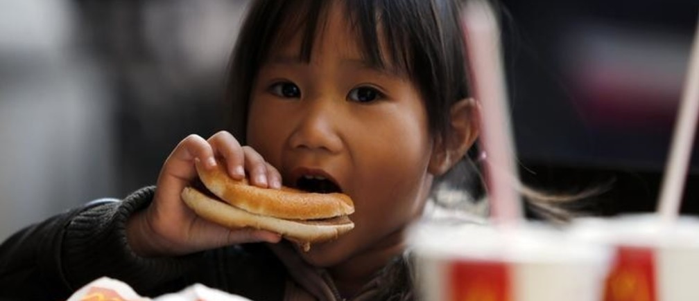 A child eats a hamburger outside a McDonald's fast food restaurant in downtown Milan October 16, 2012. The restaurant gave out meals for free before closing down after 20 years. REUTERS/Stefano Rellandini   (ITALY  - Tags: FOOD BUSINESS) ATTENTION EDITORS: ITALIAN LAW REQUIRES THAT THE FACES OF MINORS ARE MASKED IN PUBLICATIONS WITHIN ITALY