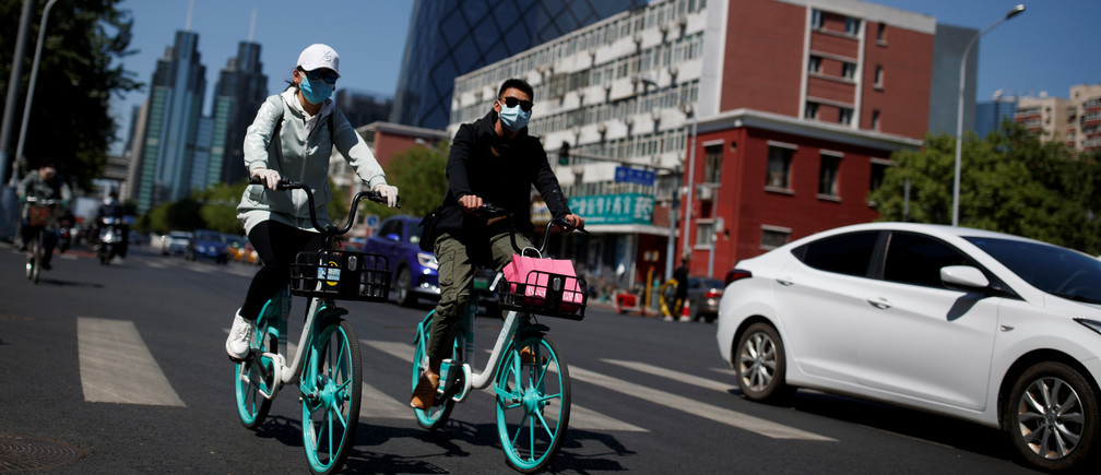 """People wearing protective masks ride bikes in the Central Business District on a """"blue sky day"""" in Beijing, as the spread of the novel coronavirus disease (COVID-19) continues, in China April 22, 2020. REUTERS/Thomas Peter - RC2M9G97ENBP"""