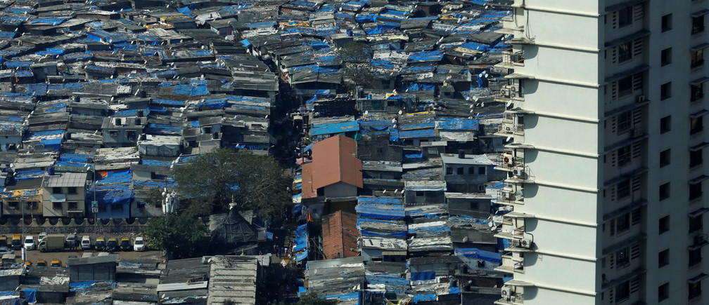 A high rise residential building is seen next to a slum in Mumbai, India