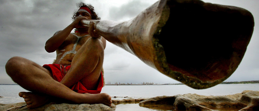 Aboriginal peformer Les Saxby plays a traditional aboriginal musical instrument known as a didgeridoo on the shores of Sydney's Botany Bay April 29, 2002 during the Meeting of Two Cultures ceremony. [The annual ceremony celebrates at the exact spot where 232 years ago the famous British explorer James Cook landed upon Australia, and is attended by local community groups as part of the ongoing reconciliation process with the local indigenous cultures.] - PBEAHUKSRBK