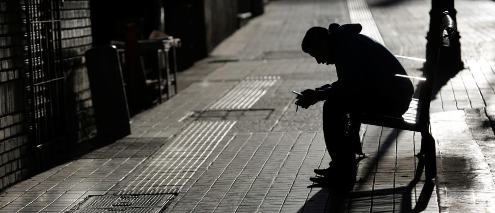 A man checks his phone while sitting on a bench in Saltillo, Mexico, November 30, 2017.